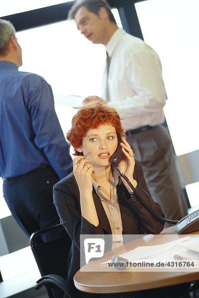 Geschäftsfrau am Tisch sitzend am Telefon  Kollegen im Hintergrund