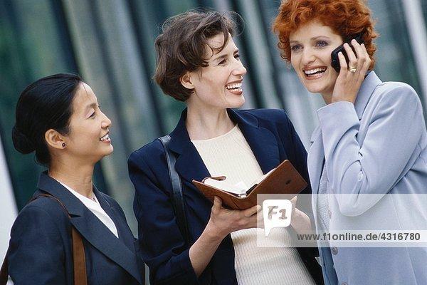 Drei Geschäftsfrauen  eine mit der Tagesordnung  eine mit dem Handy.