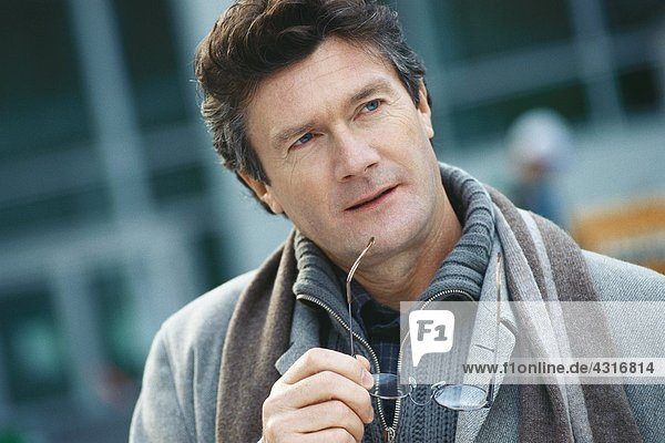 Mature man holding glasses to chin  looking away