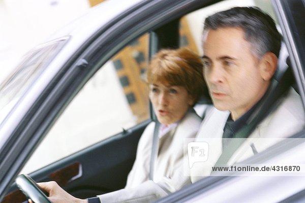 Seniorenpaar im Auto  aus dem Rahmen schauend