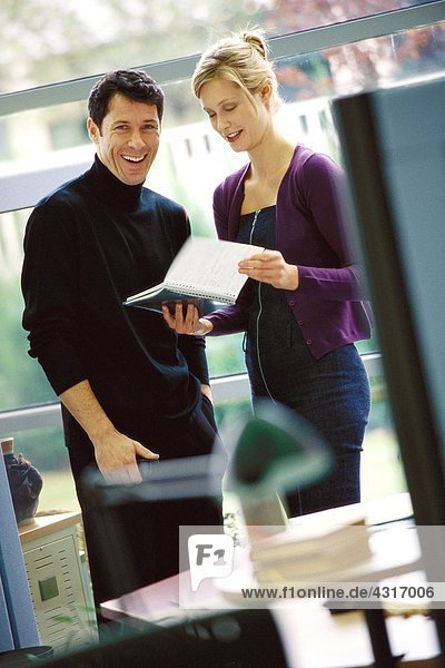 Two business colleagues looking at agenda  laughing