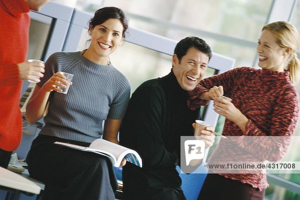 Four colleagues  holding cups of coffee and water  laughing