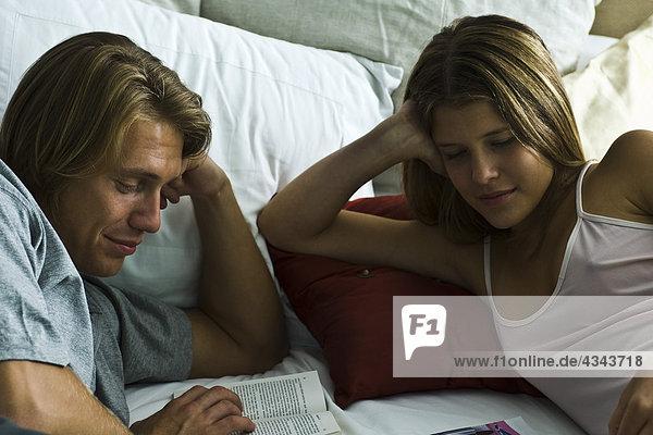 Paar zusammen liegend im Bett lesen