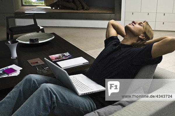 Mann entspannend auf Sofa mit Laptop-Computer in Runde