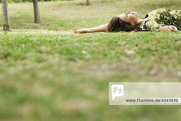 Woman lying on grass  daydreaming