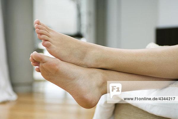 Füße einer Frau, Beine gekreuzt am Knöchel DAA052000503