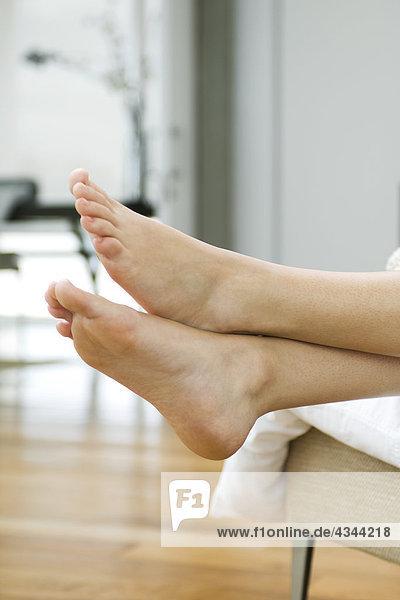 Füße einer Frau  Beine gekreuzt am Knöchel