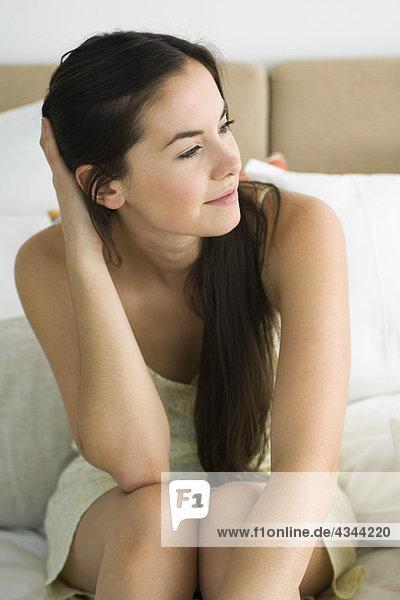 Junge Frau sitzen auf dem Bett  traumhaft Wegsehen