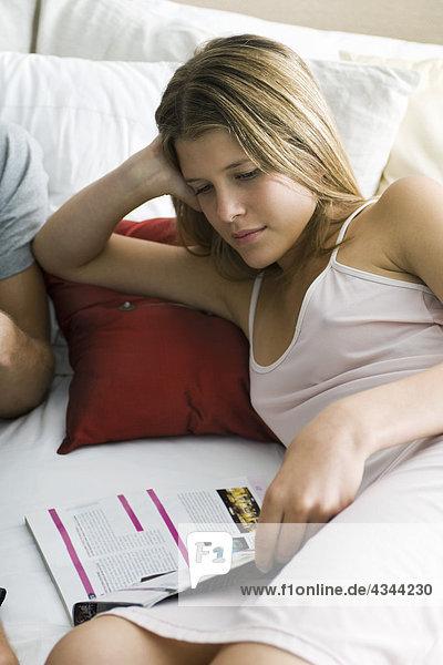 Junge Frau im Bett Magazin lesen Junge Frau im Bett Magazin lesen