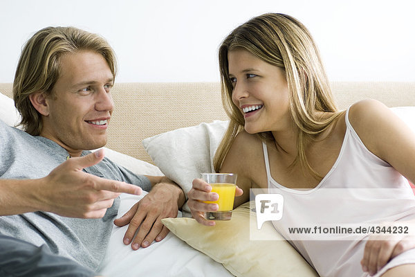 Couple talking together in bed  woman holding glass of orange juice
