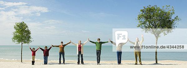 Gruppe von Menschen halten Hände in Zeile zwischen zwei Bäumen am Strand