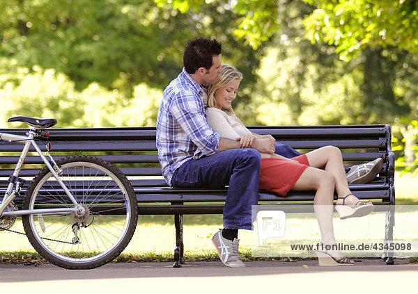 Junges Paar entspannt sich gemeinsam auf der Parkbank
