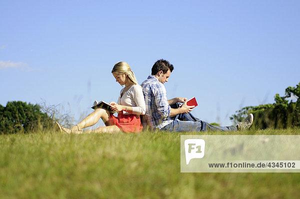 Paar sitzt Rücken an Rücken und liest im Park.