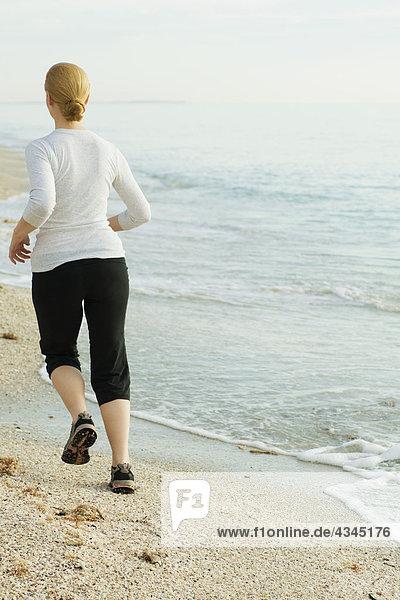 Frau beim Joggen am Strand