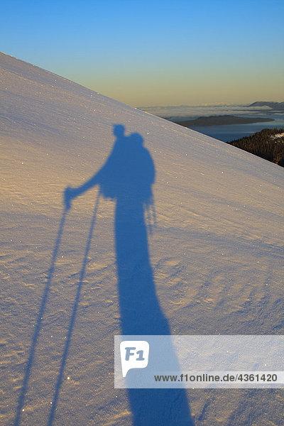 Ein Skifahrer wirft einen langen Schatten auf Schnee im Morgengrauen  wie er einen Berg auf Wrangell Island  Alaska steigt
