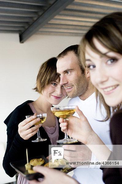 2 Frauen und ein Mann mit Champagnergläsern