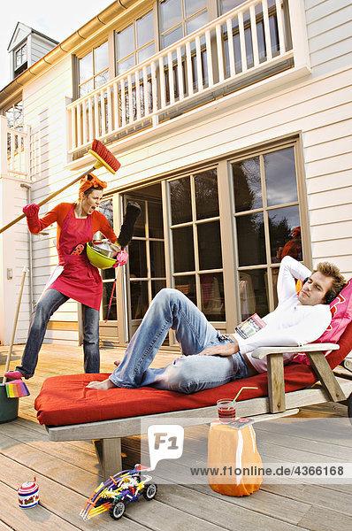 Junge Frau mit Reinigungszubehör schreit den auf einem Liegestuhl liegenden Mann an.