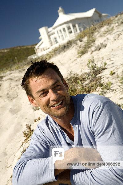 Porträt eines lächelnden Mannes  der am Strand sitzt.