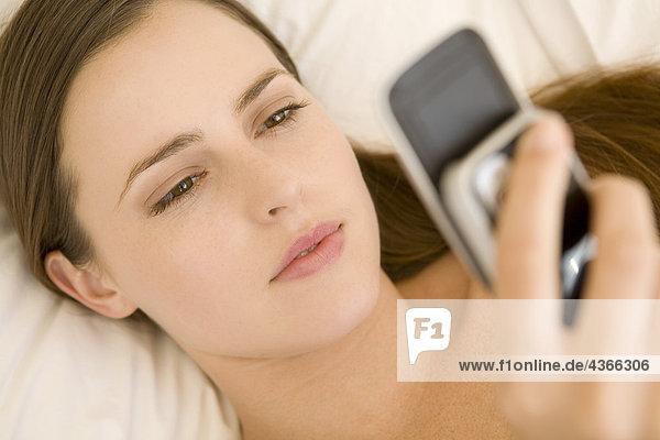 Porträt einer jungen Frau  die auf einem Bett liegt und ihre Zelle hält.