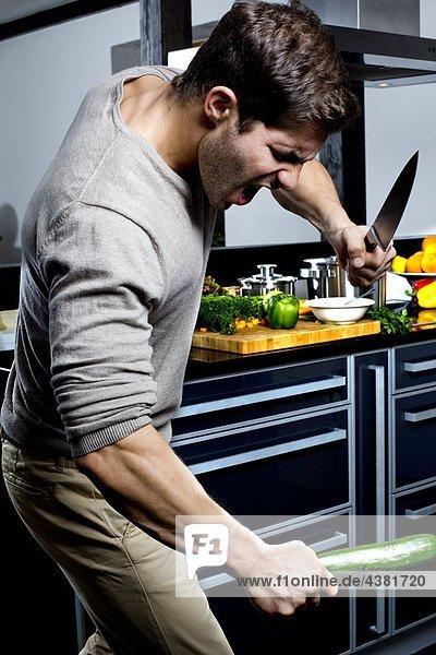 Junger Mann steht wütend in der Küche