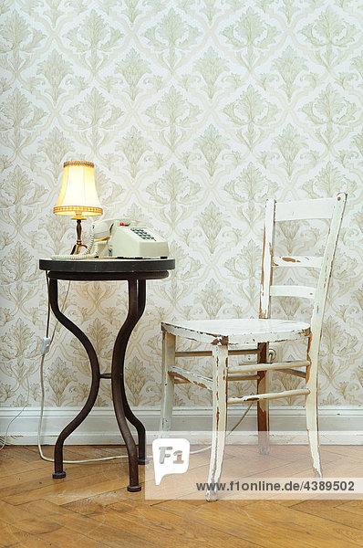 Stuhl und Tisch mit Lampe und Telefon