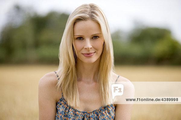 Ein Porträt von eine blonde kurzhaarige Frau in ein Weizenfeld