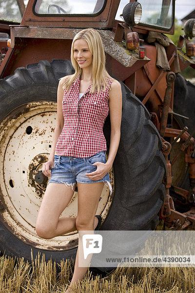 Eine blonde Frau an einem Traktor gelehnt