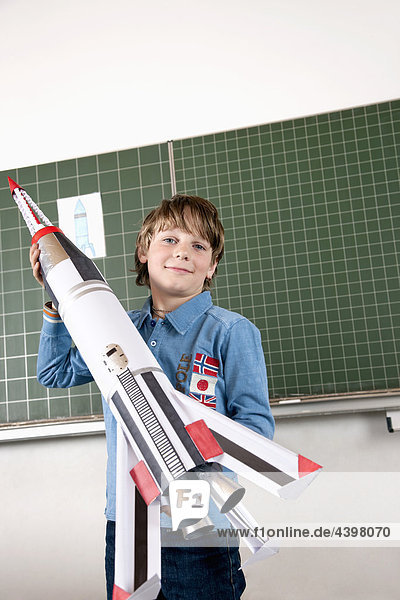 portrait of young boy in classroom holding model of rocket