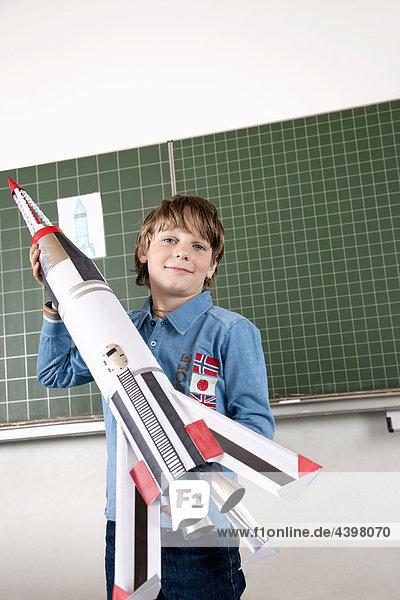Porträt der jungen im Klassenzimmer mit Modell-Rakete