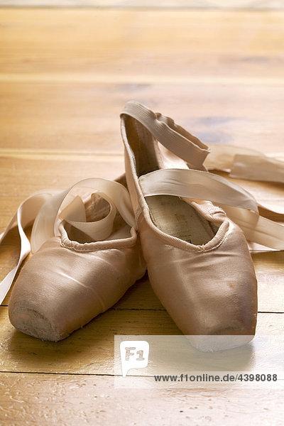 paar Ballettschuhe auf Holzfußboden
