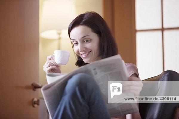 Interior  zu Hause  Portrait  Frau  jung  trinken  Kaffee  Zeitung  vorlesen