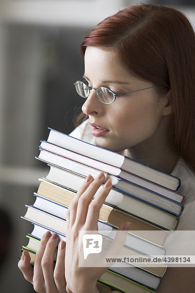 Porträt von weiblichen Studenten tragen Haufen Bücher Porträt von weiblichen Studenten tragen Haufen Bücher