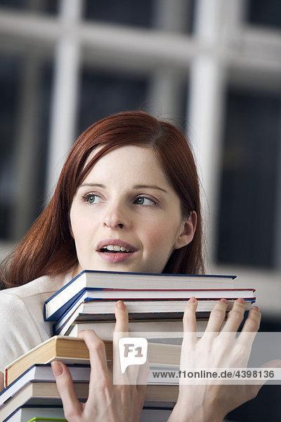 Porträt von weiblichen Studenten tragen Haufen Bücher