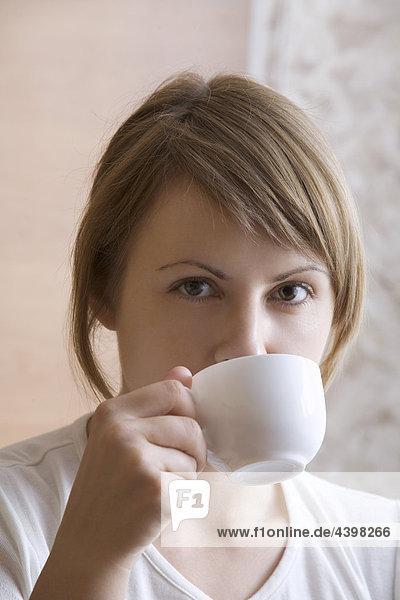 Portrait einer jungen Frau trinken aus cup Portrait einer jungen Frau trinken aus cup