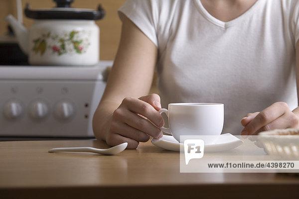 Detail der junge Frau sitzen am Tisch mit cup