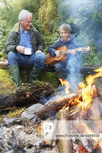 Großvater und Enkel am Lagerfeuer