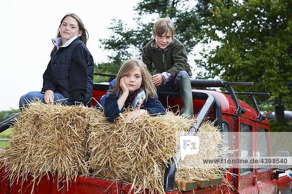 Children sitting on 4x4 landrover
