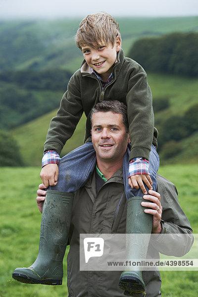 Vater gibt dem Sohn ein Huckepack im Feld.