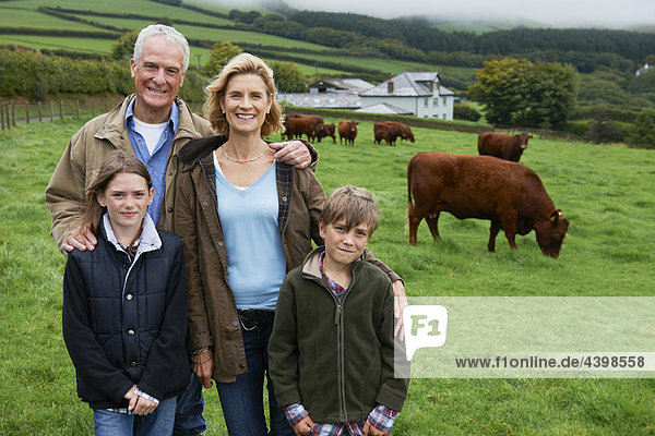 Family on farm in a field with cows