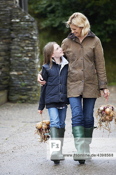 Grandmother and girl carrying vegetables