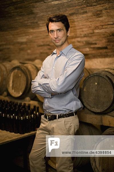 Mann im Weinkeller stehend