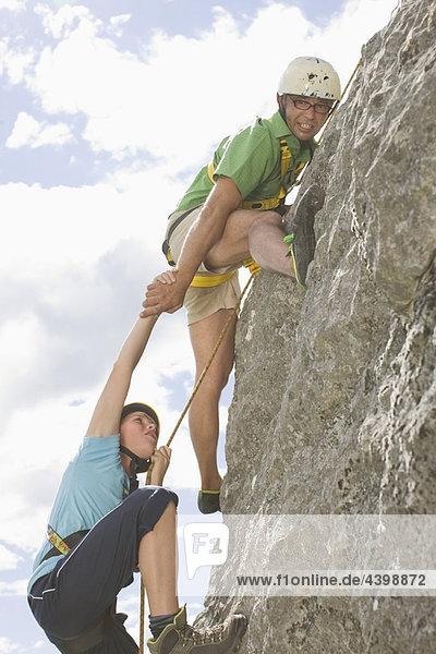 Jungen klettern auf einen Felsen