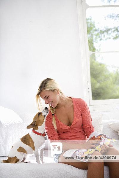 Junge Frau zu Hause mit Hund auf der Couch