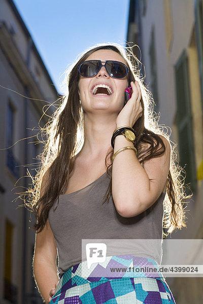 Frau spricht auf dem Handy in der Straße