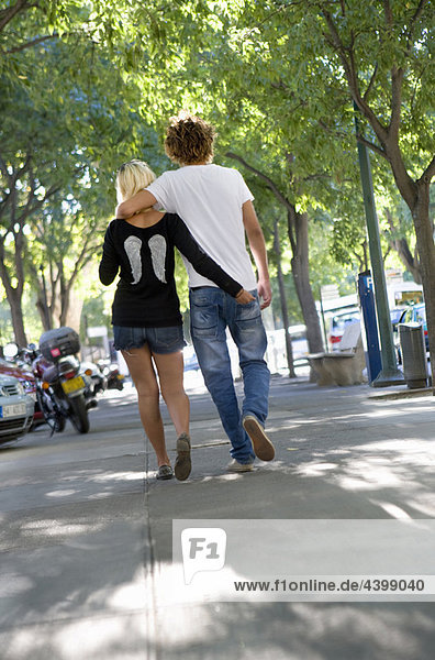Young loving couple walk in street