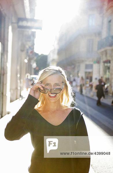 Frau schaut über Sonnenbrille in der Straße