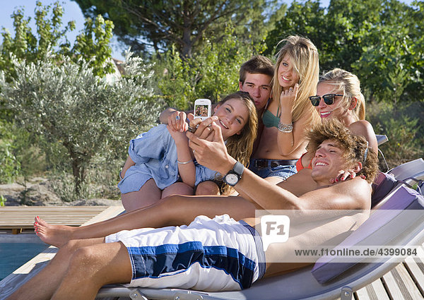 Teenagergruppe am Pool macht Telefonfoto