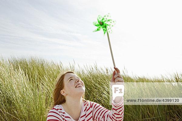 Mädchen hält Kinderwindmühle in Dünen hoch