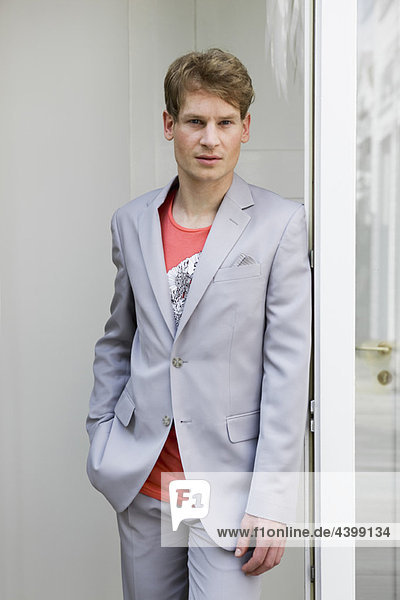 Young man leaning on door