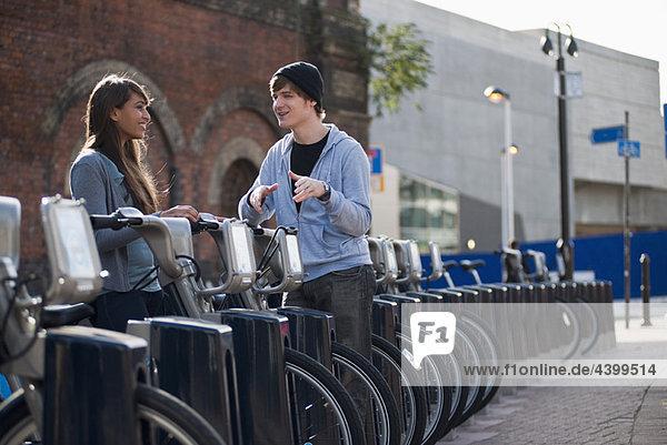 Junges Paar im Gespräch mit dem Leihfahrrad